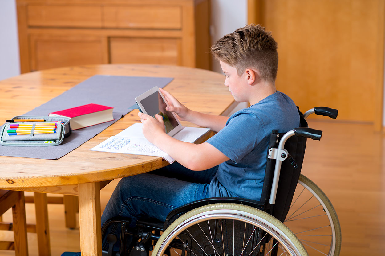 Inklusion: Junge im Rollstuhl macht Hausaufgaben. Foto: Panthermedia